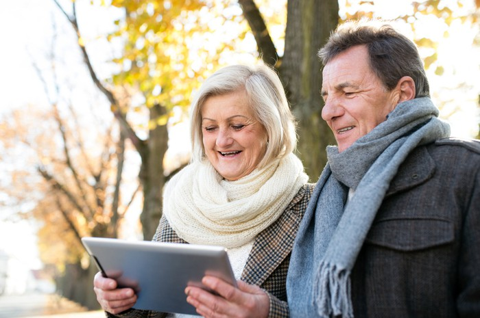 Senior couple looking at a tablet outdoors