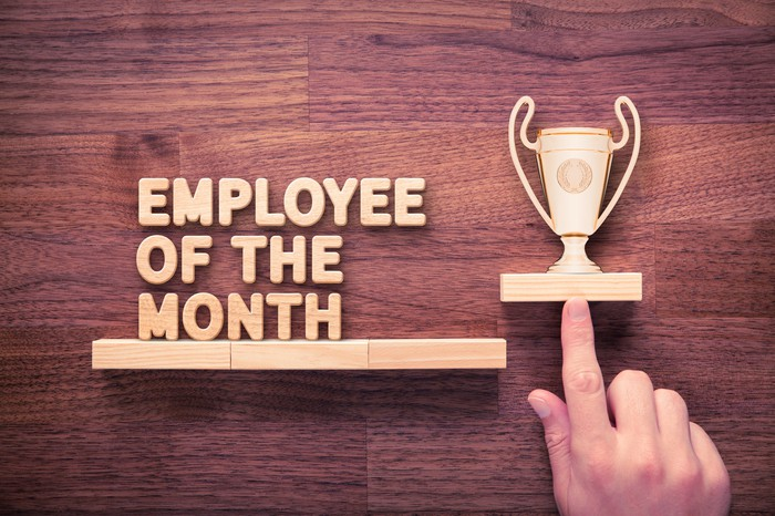 "A finger points to a wooden trophy, which sits next to the words ""Employee of the Month."""