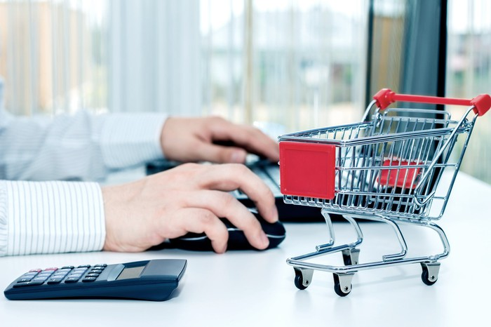 Man working at computer with calculator and a model of a shopping cart next to him.