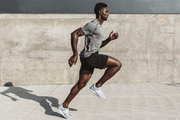 Man running down sidewalk wearing Lululemon's Metal Vent Tech running top.