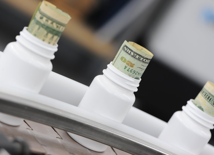 A drug manufacturing line with cash sticking out the tops of pill bottles.