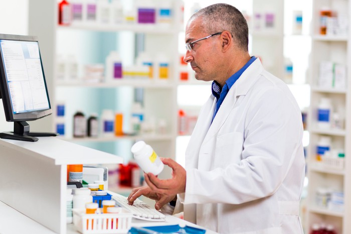 A pharmacist looks at a computer monitor while holding a pill bottle in one hand and typing with the other.