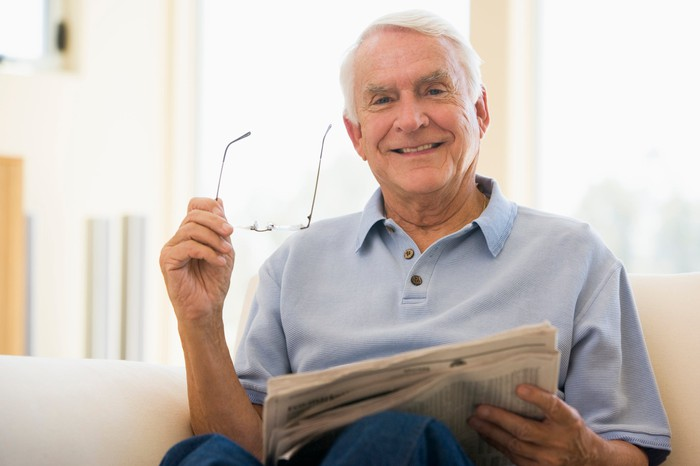 A senior man sits on a sofa and smiles, holding a newspaper in one hand and reading glasses in another.