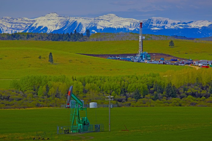 Drilling rig and pump jack with mountain range in background