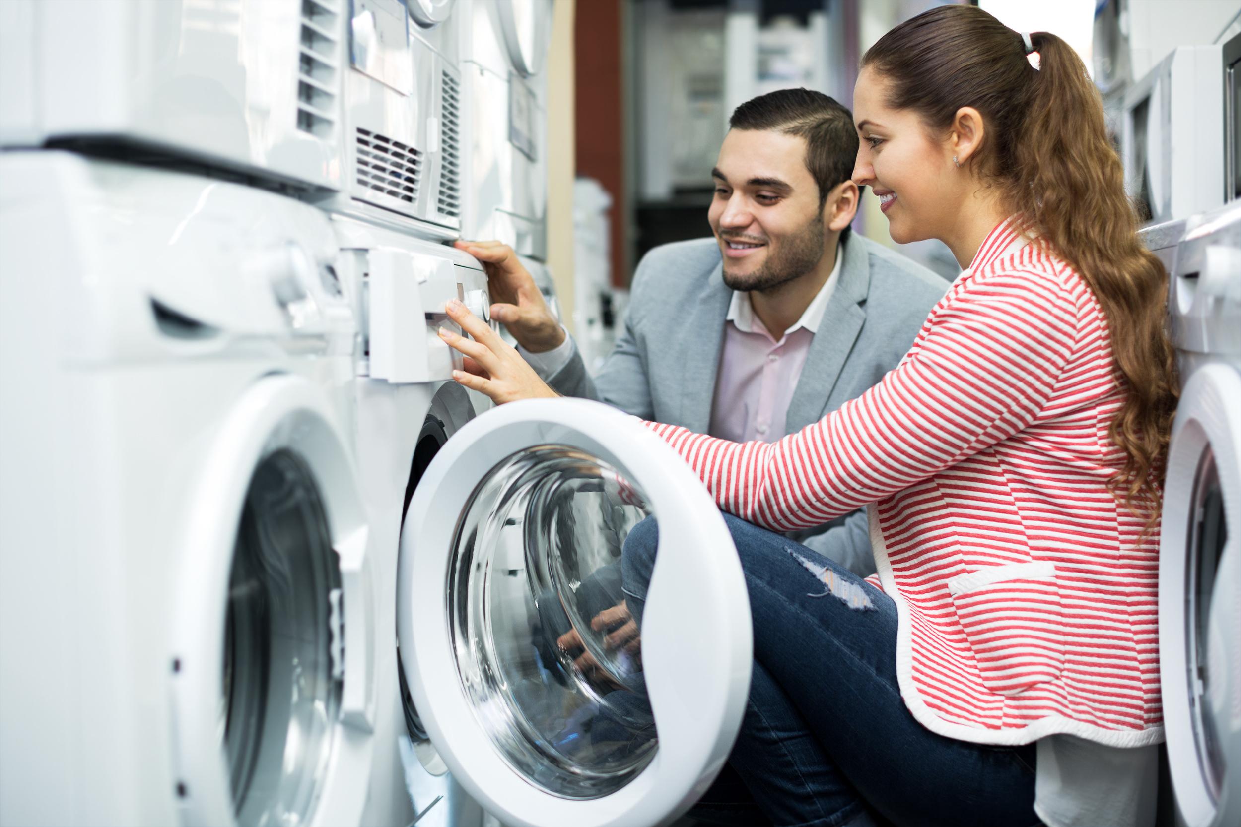 A woman and man look at washing machines