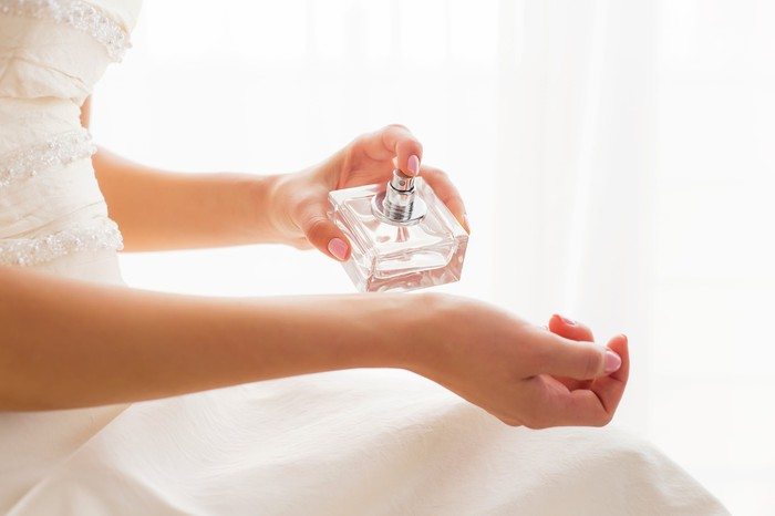 A bride sprays perfume on her wrist