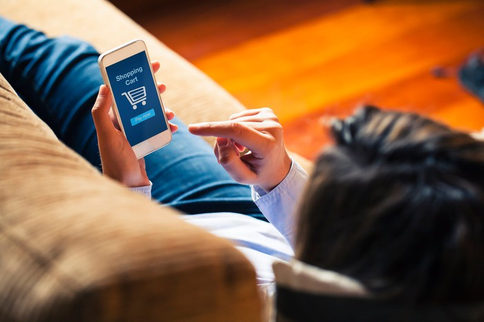 Woman shopping by mobile phone lying on a couch.