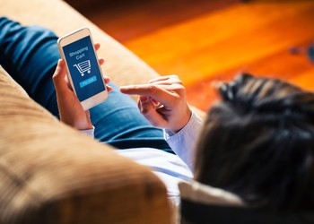 Woman shopping by mobile phone laying at home.