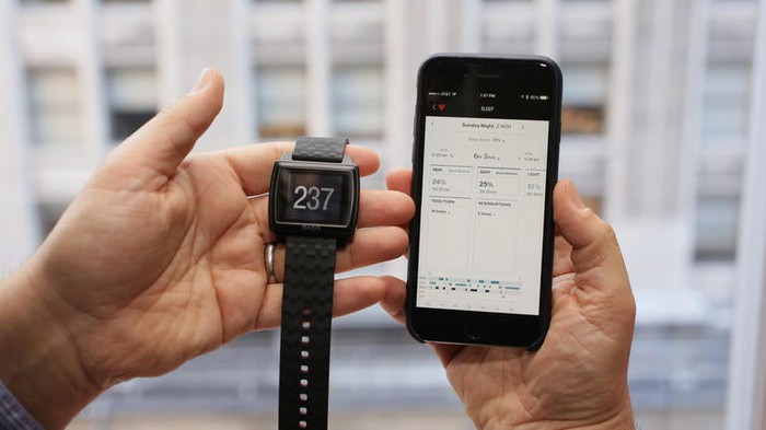 A Basis Peak watch next to a smartphone.