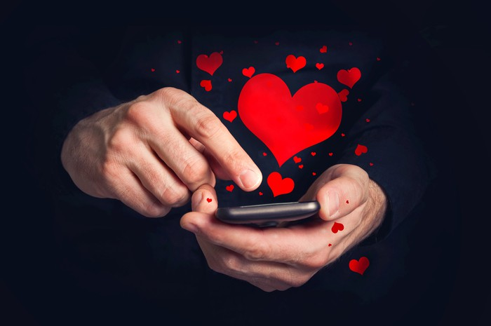 Two hands, one holding a cellphone, one swiping the screen from which red hearts are floating.