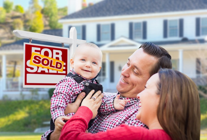 """A man and woman smile at their child in arms, next to a """"sold"""" sign in front of a house."""