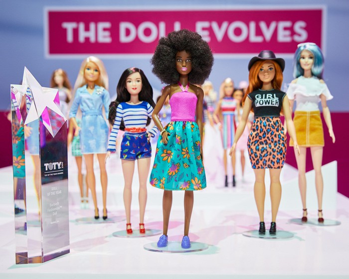 """A lineup of diverse dolls standing in front of a banner reading """"The Doll Evolves"""" with the Doll of the Year Award."""