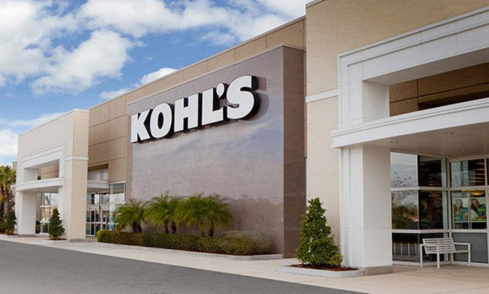 A freestanding Kohl's store with a light brown exterior and small trees in front