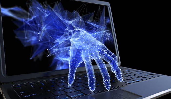 A hand reaching out from a computer screen to touch the keyboard.