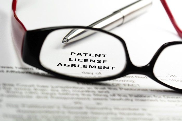 A pair of glasses on top of a patent licensing agreement.