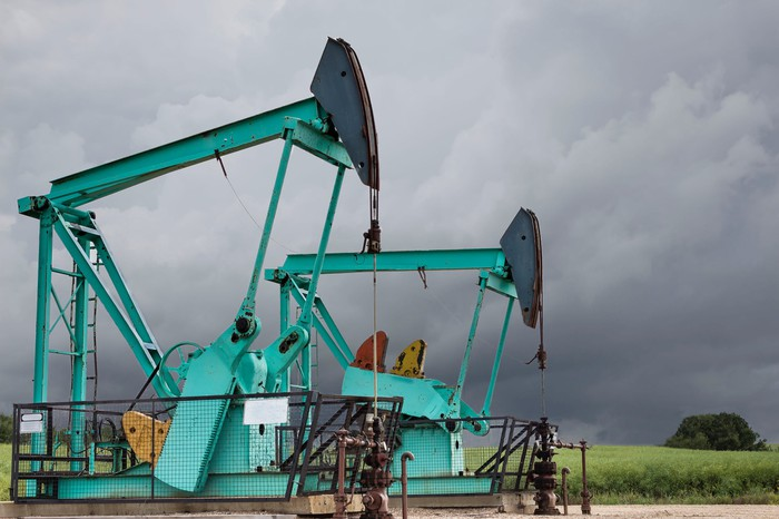 Two green oil wells sitting under a dark stormy grey sky in the summer time.