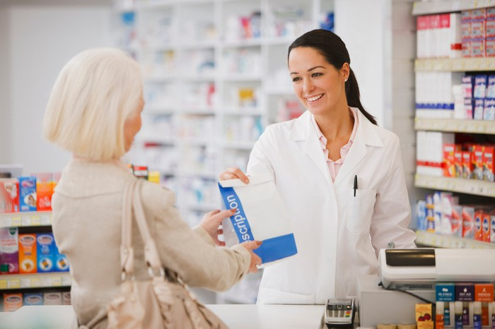 A pharmacist hands a bag containing a prescription to a customer.