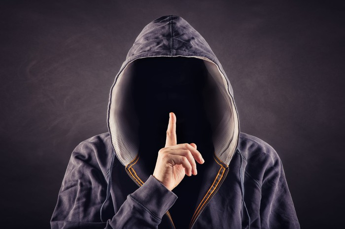 A hooded person holding his finger over his lips