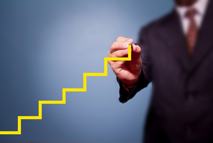 A man in a suit draws a stairstep pattern in yellow, signifying a stock chart showing growth.