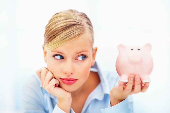 A millennial looking at her piggy bank.