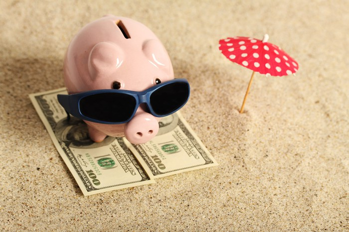 Surrounded by sand and next to a tiny red umbrella with white polka dots, a piggy bank with sunglasses sits on two hundred-dollar bills, resembling a beach blanket.