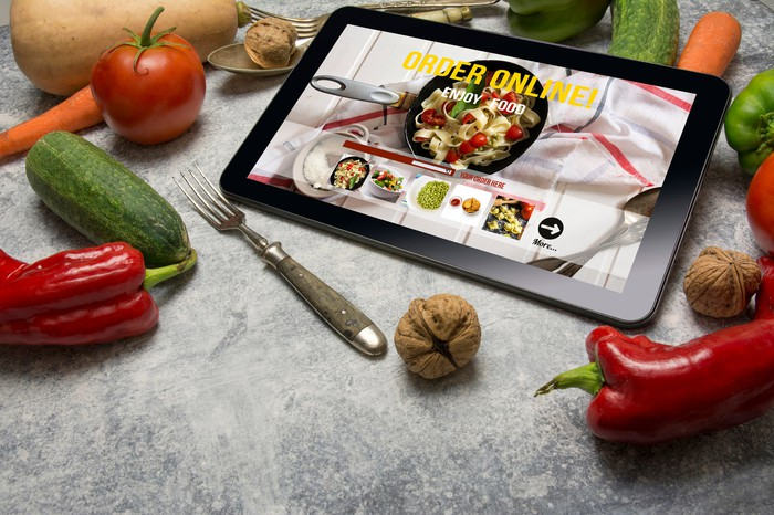 Tablet with Online food delivery app on screen