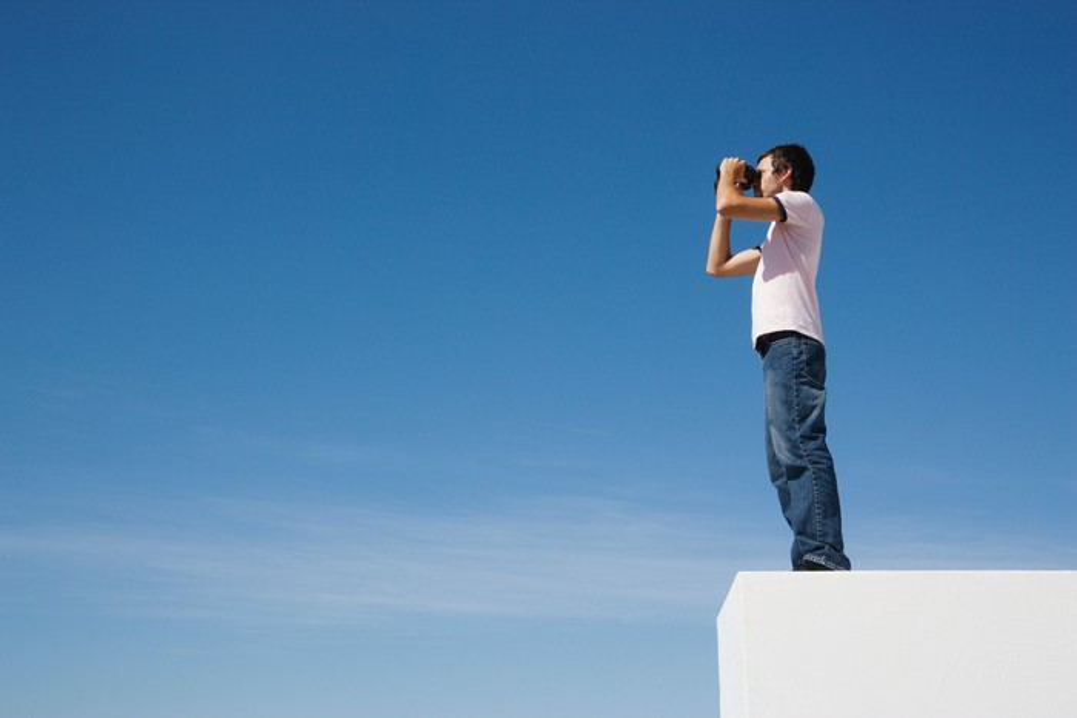 Man looking through a pair of binoculars.