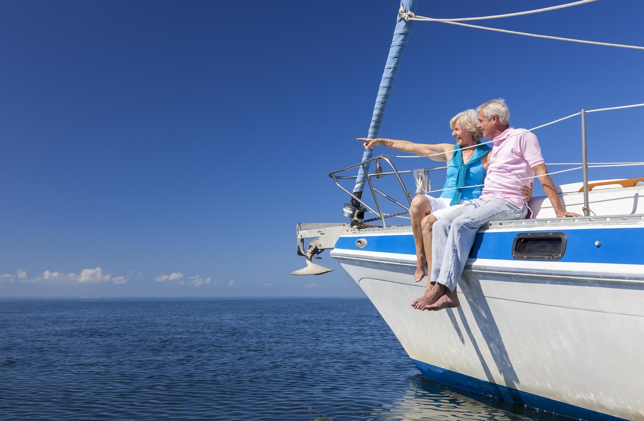 Senior couple sitting on edge of sailboat