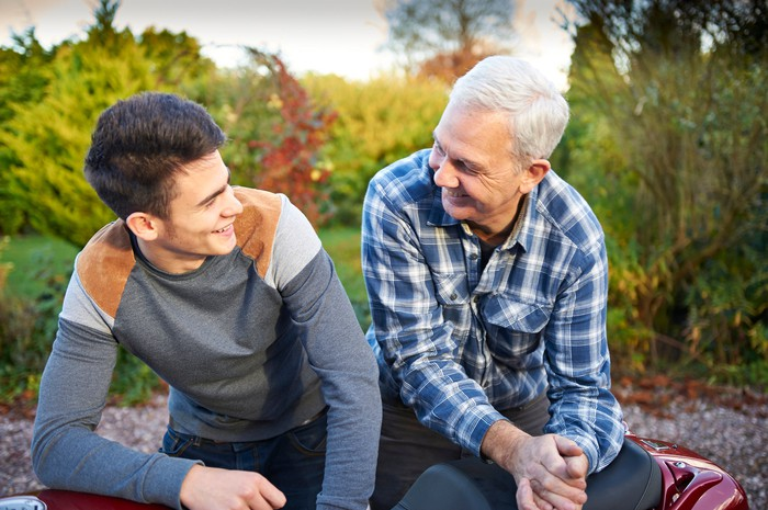 Young man sitting with grandfather and smiling
