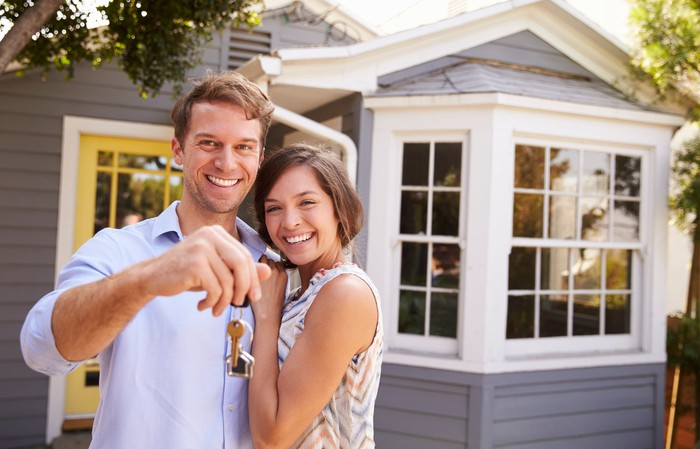Couple holds keys in front of house.