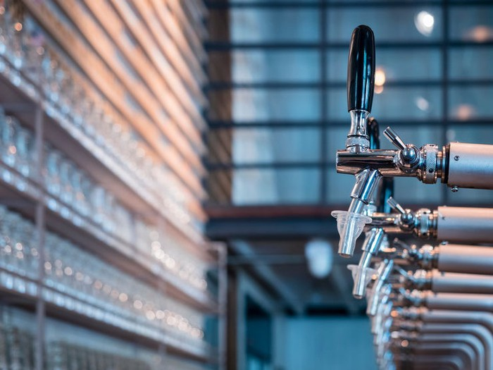Line of chrome and silver beer taps in an industrial style bar.