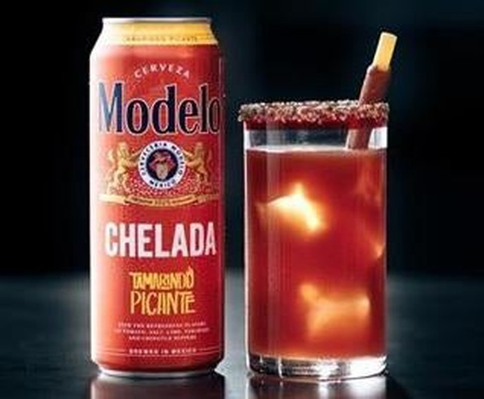 "Festive can of Modelo Chelada ""Tamorindo Picante"" next to a glass filled with the reddish orange beverage, black background."