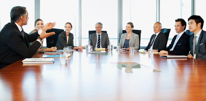 People in business attire around an apparent boardroom table