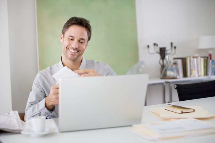 A man opening mail at a computer