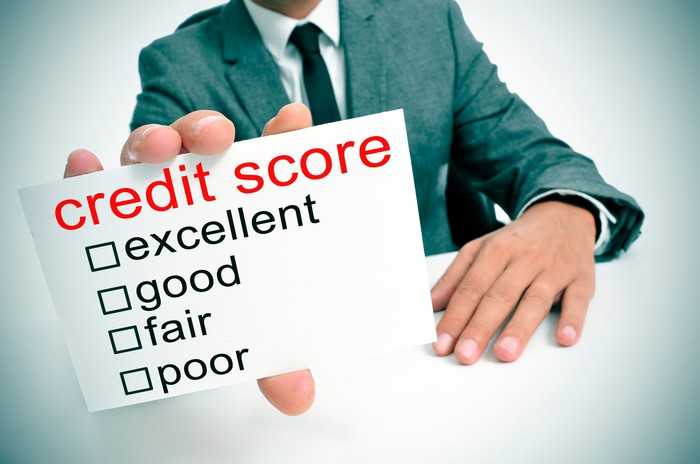 "A man holds in his hand a card with the words ""credit score"" in red, followed by ""excellent,"" ""good,"" ""fair,"" and ""poor"" with check boxes next to each."