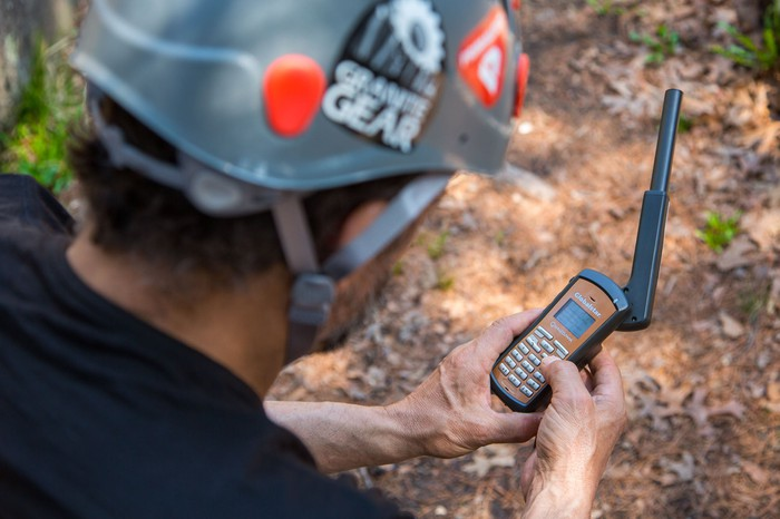 A man hiking in the wilderness using a Globalstar satellite phone.