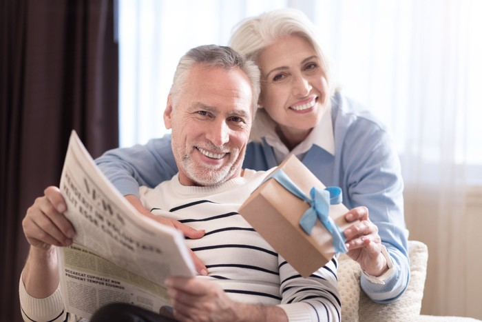Baby-boomer couple reading the newspaper.