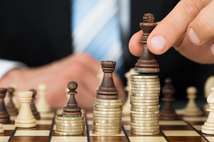 A man's hand places a chess piece on the tallest of successively higher stacks of coins.