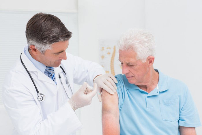 An elderly man receives an injection from a doctor.