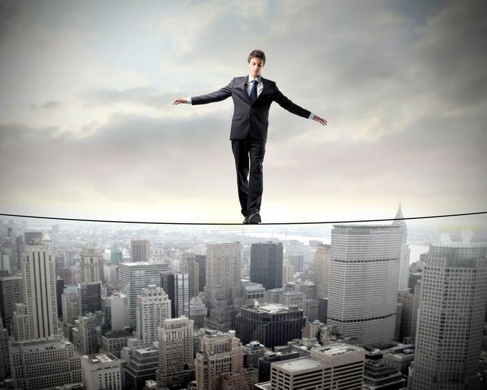 A businessman walks a tightrope, with a city skyline beneath him.