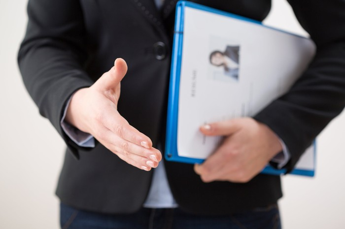 A person holding a folder puts a hand out to shake.