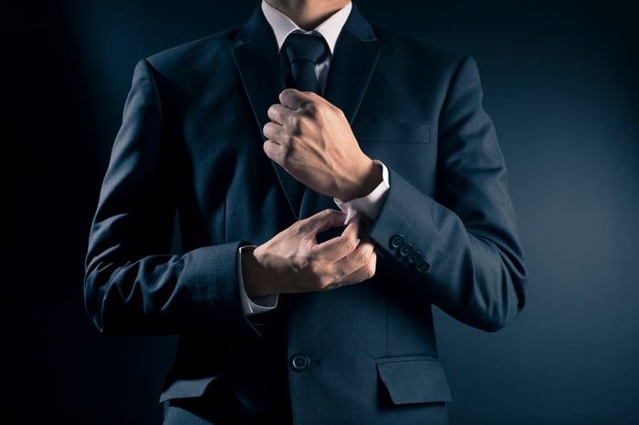 A man in a sut fixes his cuff.