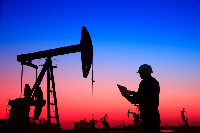 An oil-field worker with a laptop stands beneath a pumpjack at sunset.