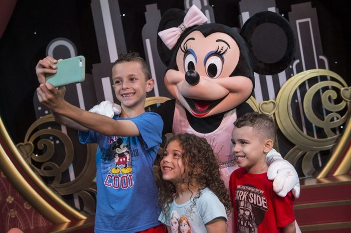 Minnie Mouse taking photos with kids at Disney World.