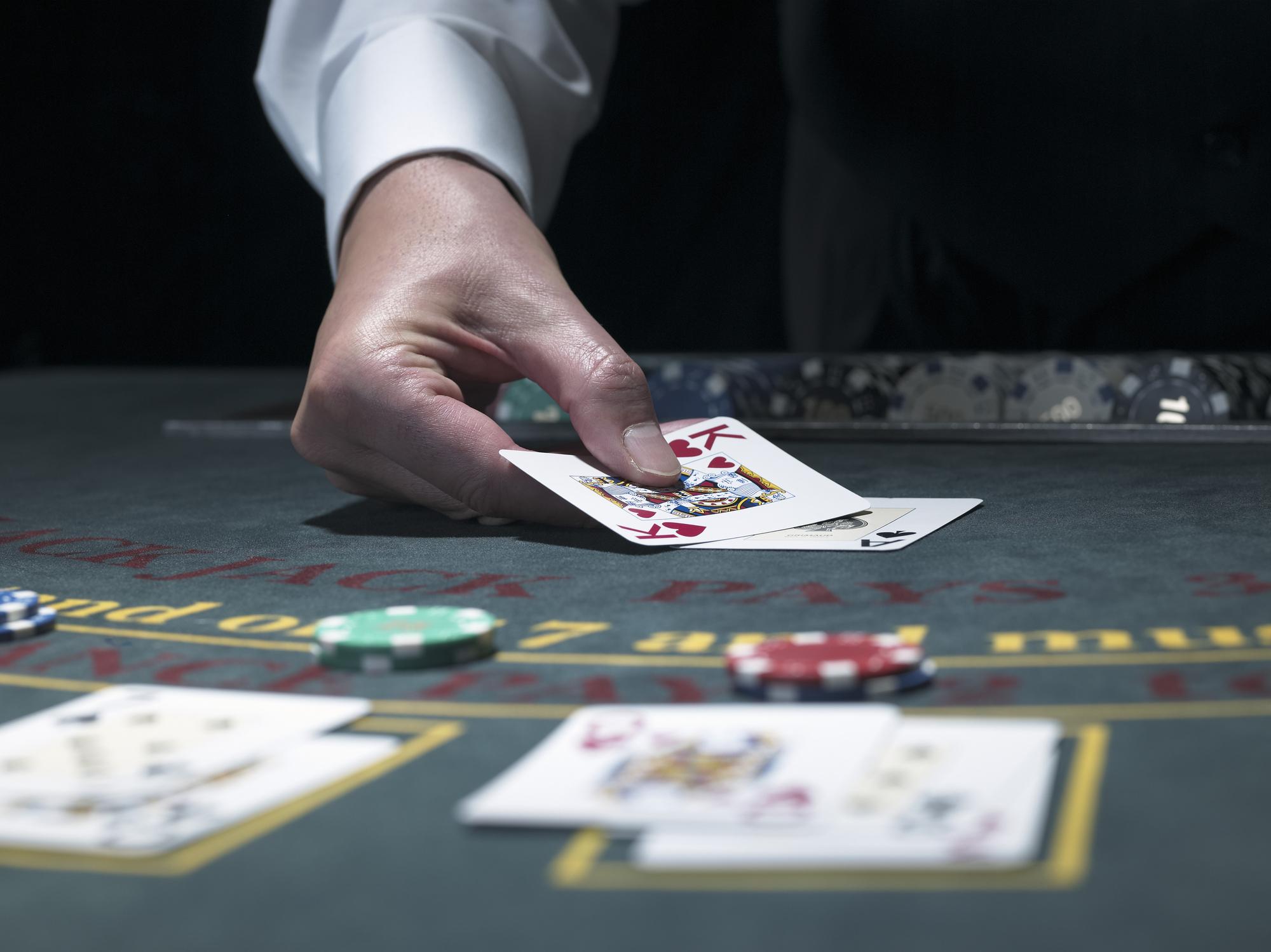 A blackjack dealer puts cards on the table.