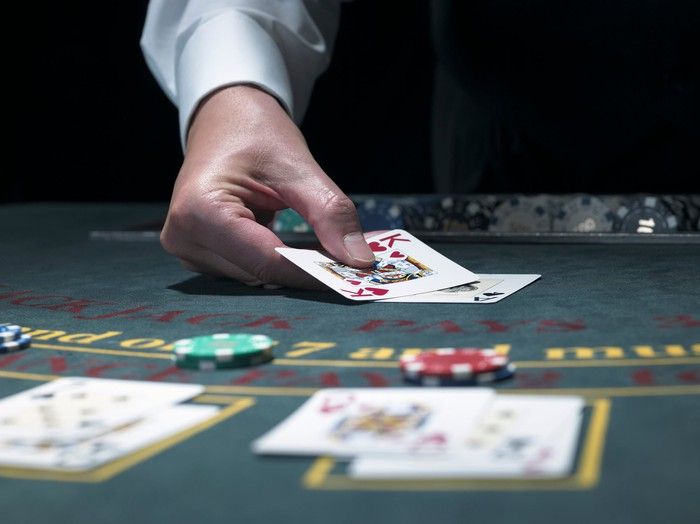 A blackjack dealer puts cards on the table.