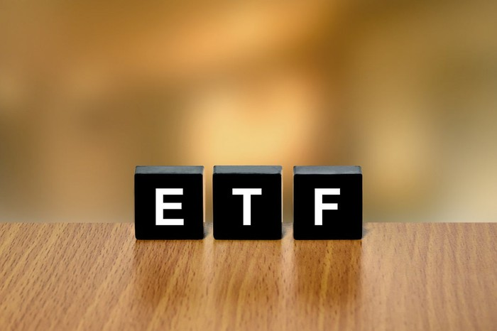 "Letter blocks standing upright on a tabletop spell out the word ""ETF."""