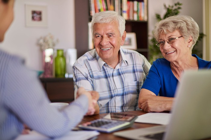 Retired couple talking with another person