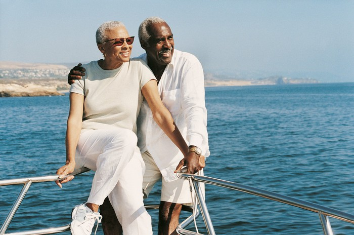 Senior couple standing on boat looking toward the sun and smiling