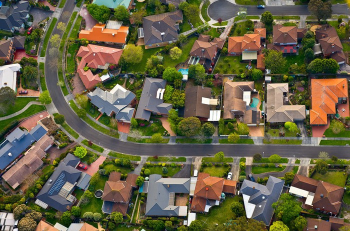 Aerial shot of a densely packed neighborhood along a winding road